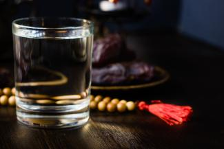 Photo depicts a glass of water and prayer beads on a table